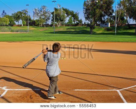 Boy Hitting A Baseball