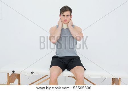 Portrait of a handsome young man wearing cervical collar in the medical office