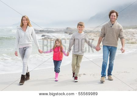 Full length portrait of a happy family of four walking hand in hand at the beach