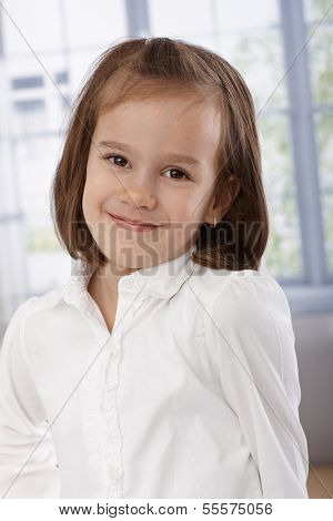 Portrait of adorable little girl smiling, looking at camera.