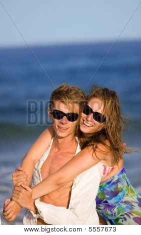 Happy Smiling Young Couple  On The Beach