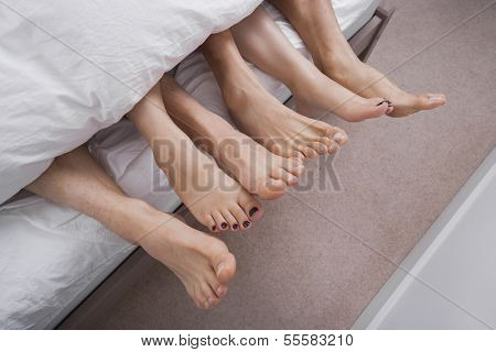 Low section of woman with two men in bed
