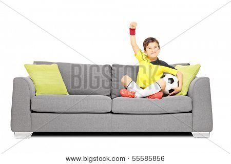 Happy boy in sportswear with a soccer ball sitting on a sofa and gesturing happiness isolated on white background