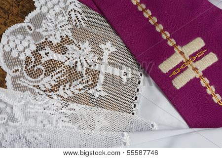 Purple priest stole used for confessions lying on a white lace surplice