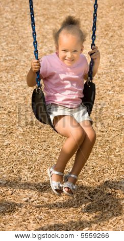 Beautiful Little Mixed Race Girl On Swing With Smile
