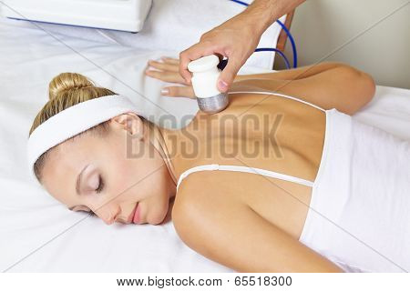 Young woman in spa getting electric back massage