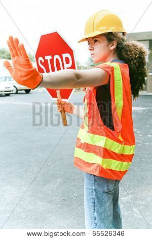 Young female construction apprentice holding a stop sign and directing traffic.