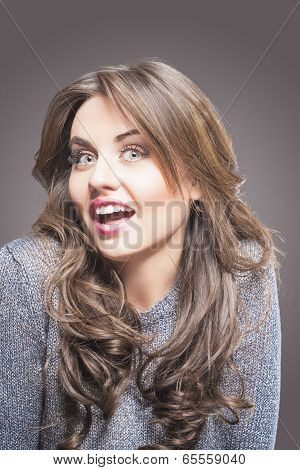 Happy And Flippant Young Woman In Gray Sweater On Grey Background