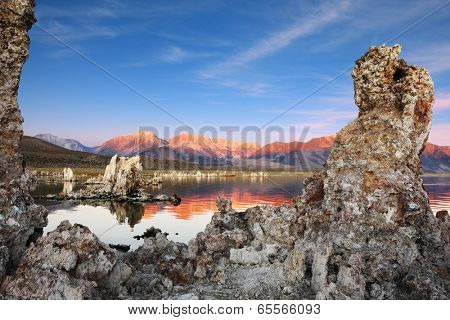 Outliers - bizarre limestone calcareous tufa formation on the smooth water of the lake. The magic of Mono Lake. Orange sunset