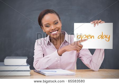 Happy teacher holding page showing open day in her classroom at school