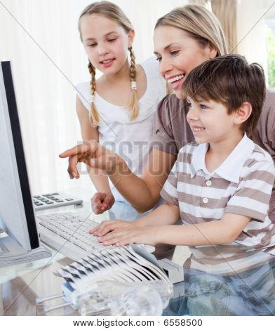 Happy Mother And Her Children Using A Computer