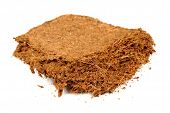 A piece of coconut coir brick (used as a growing medium or soil amendment) isolated on a white background poster