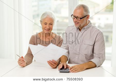 family, business, savings, age and people concept - smiling senior couple with papers and calculator at home