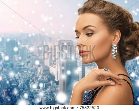 people, holidays, christmas and glamour concept - beautiful woman in evening dress wearing ring and earrings over snowy city background
