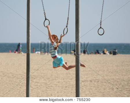 Girl swinging with the beach in the background poster