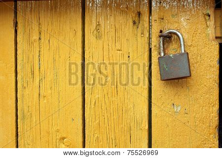 Padlock On Yellow Wooden Door