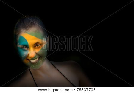 Portrait of a woman with the flag of the Brazil painted on her face - Latin America