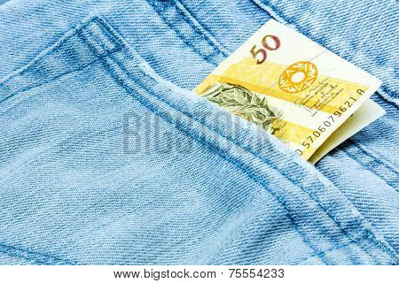 Creative composition of Brazilian Money (Reais) on the jeans