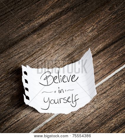 Believe in yourself written on the paper on a wood background