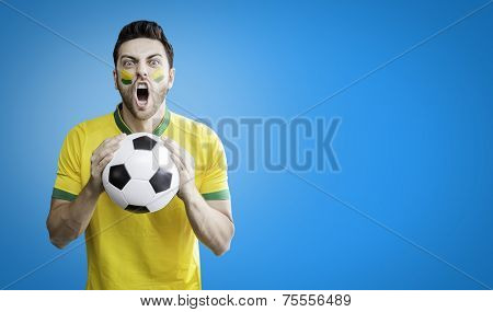 Brazilian man holding a soccer ball celebrates on the blue background