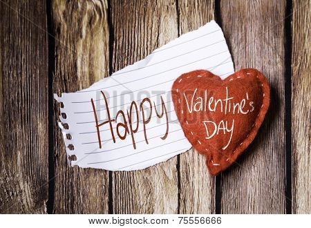 Happy Valentine's Day written on a peace of paper and a heart on a wooden background