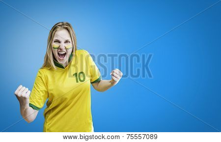 Brazilian woman celebrates on blue background with her face painted. Can be used as Australian uniform too.