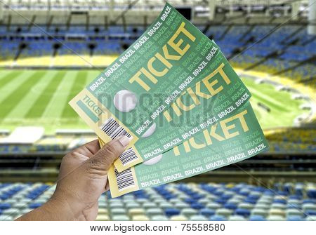 Hand holds a homemade soccer tickets on an empty stadium