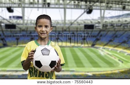 Brazilian little boy holds a soccer ball on the stadium