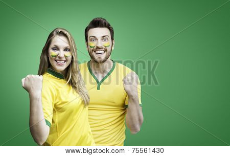 Brazilian couple fan celebrate on green background