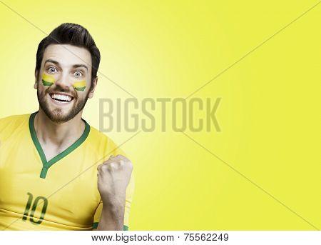 Brazilian soccer fan celebrates on yellow background
