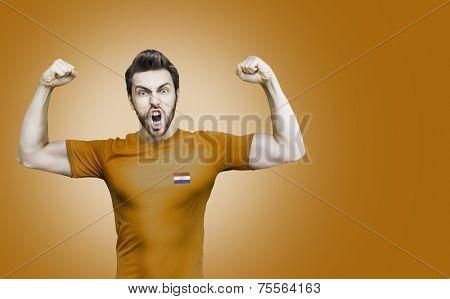 Dutchman soccer player celebrates on orange background