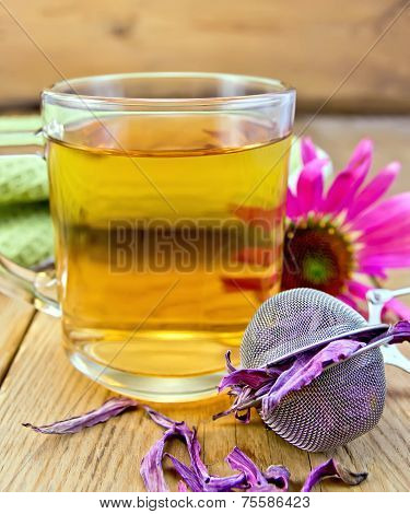 Tea from Echinacea in glass mug with strainer on board