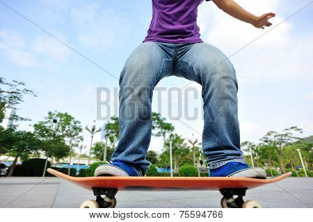 young woman skateboarder skateboarding at  modern city