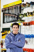 Portrait of confident male customer standing arms crossed in hardware shop poster