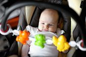 Little two month baby playing in a carseat poster