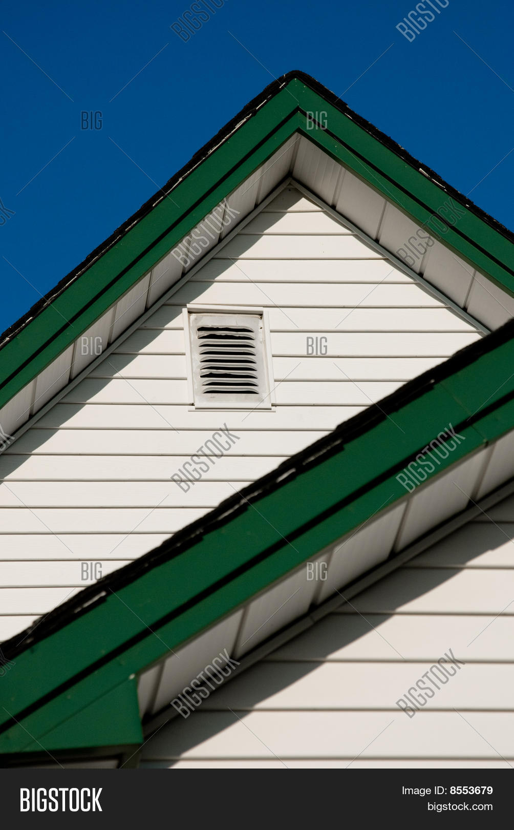 Farmhouse Roof Peak With White Siding And Green Trim Against A Blue Sky
