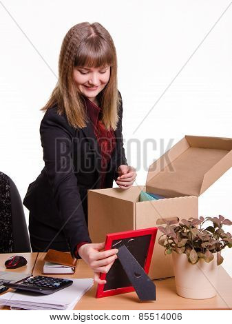 Girl Puts A Photo Frame On Desktop In Office