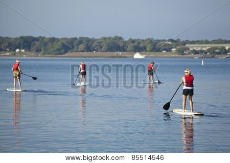 women paddleboarding on open water, focus on closest woman