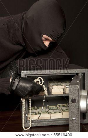 Thief burglar stealing dollar money during home safe code breaking
