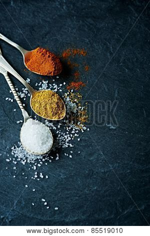 Ground  pepper, curry powder and rock salt on spoons