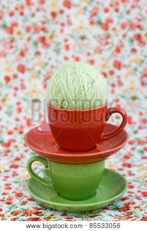 Two Colorful Cups And Balls Of Yarn On A Background Of A Red Flower