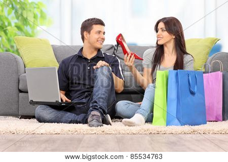 Woman showing her new shoes to boyfriend at home