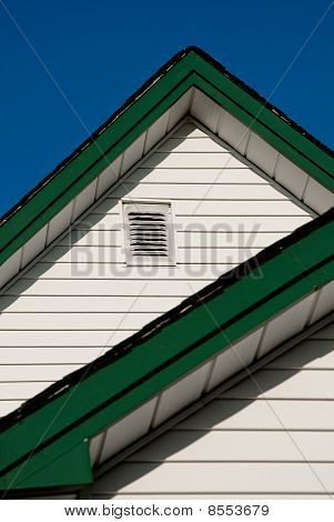 Farmhouse Roof Peak With White Siding And Green Trim Against A Blue Sky.