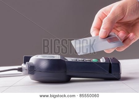 Man using card to express pay against grey background