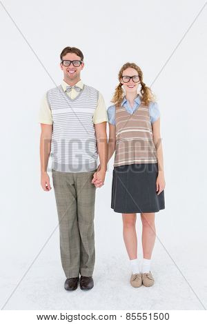 Smiling geeky hipster couple holding hands on white background