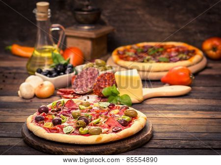 Homemade pizza with ham, cheese, vegetables and pizza ingredients on the table