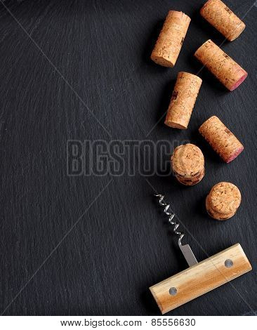 Background of several wine corks with a wooden cork screw