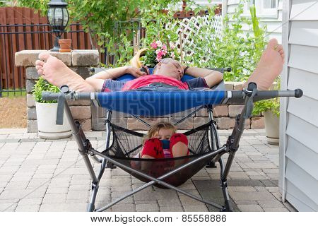 Father And Daughter Relaxing Together On The Patio