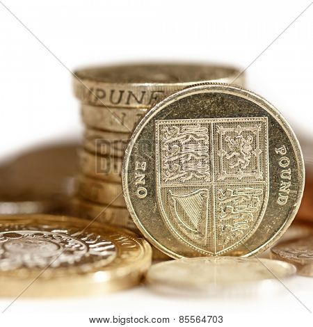 British coins, with focus on one pound.  White background.