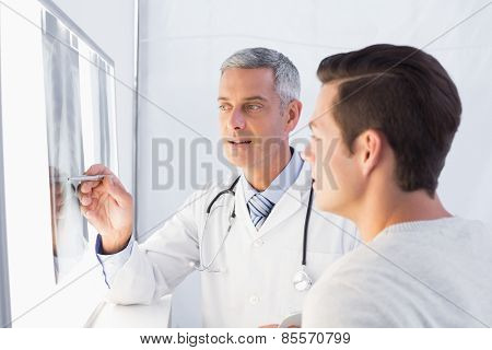 Doctor showing X rays to his patient in medical office